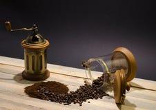 Cafè moulu dispersé de grains de café et broyeur de café manuelle sur les conseils en bois et sur le fond noir image stock