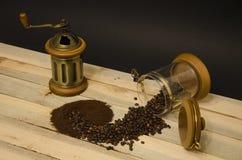 Cafè moulu dispersé de grains de café et broyeur de café manuelle sur les conseils en bois et sur le fond noir image libre de droits