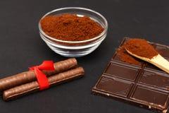 Cafè moulu et chocolat sur le fond noir et le café empilé frais sur la cuillère en bois Photo libre de droits