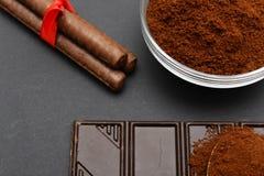 Cafè moulu et chocolat sur le fond noir et le café empilé frais sur la cuillère en bois Image libre de droits