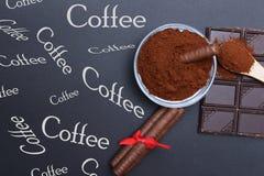 Cafè moulu et chocolat sur le fond noir et le café empilé frais sur la cuillère en bois Images libres de droits