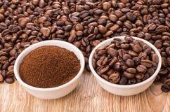 Café à terra e feijões de café roasted em umas bacias na tabela Imagens de Stock