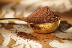 Café à terra na colher dourada imagem de stock royalty free
