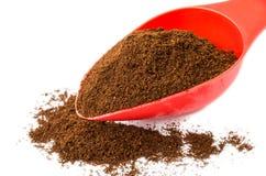 Café à terra na colher e no montão vermelhos do café Imagem de Stock Royalty Free