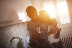 Café étreignant et potable de beaux jeunes couples dans la cuisine Images libres de droits