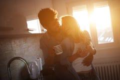 Café étreignant et potable de beaux jeunes couples dans la cuisine Photo libre de droits