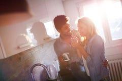 Café étreignant et potable de beaux jeunes couples dans la cuisine Image libre de droits