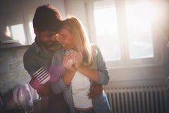 Café étreignant et potable de beaux jeunes couples dans la cuisine Photos stock