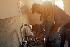 Café étreignant et potable de beaux jeunes couples dans la cuisine Photographie stock