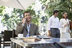 Café al aire libre de Using Cellphone At del hombre de negocios foto de archivo libre de regalías