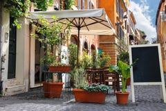Café al aire libre en una calle estrecha en Roma, Italia imagen de archivo libre de regalías