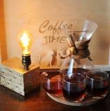 Café alternativo que prepara en el filtro Cubiletes de cristal Lámpara de mesa con el bulbo de Edison Imagenes de archivo