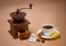Café-amoladora y taza de café caliente Imagenes de archivo