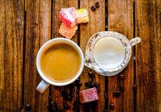 Café aromatique dans une tasse blanche avec une cruche de lait en verre à côté de elle, photo stock