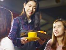 Café asiatique de sourire de portion de serveuse de jeunes aux clients photos stock