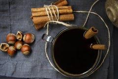 Café avec des bâtons et des écrous de cannelle sur une serviette de toile Configuration plate Photographie stock