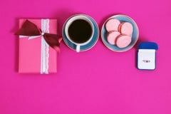 Café avec des macarons et anneau sur un fond rose Une offre de mariage, boîte qui donnent l'anneau Vue supérieure, image modifiée Images stock