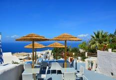 Café avec des parapluies sur le fond de la mer et les palmiers, l'île de Santorini, Grèce. Photographie stock libre de droits