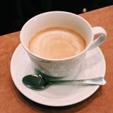 Café avec du lait de mousse dans le service blanc de tasse du plat blanc Photo stock