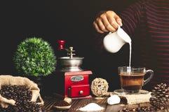 Café avec du lait se renversant en verre sur un en bois photo libre de droits