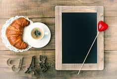 Café avec la décoration de croissant, de tableau noir et de coeur Photos stock