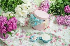 Café avec la mousse et fleurs blanches et pivoines roses sur un voile léger en fleurs Photos stock