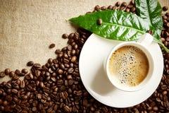 Café avec la tasse de mousse avec des haricots dans le coin avec la feuille verte sur le lin image stock