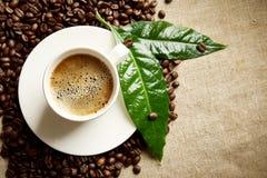 Café avec la tasse de mousse avec des haricots du côté gauche avec la feuille verte sur le lin photographie stock libre de droits