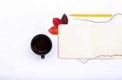 Café avec le bloc-notes ouvert, le crayon et les feuilles d'automne colorées Photos stock