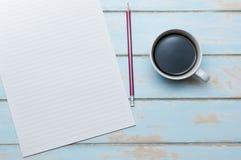 Café avec le papier à lettres et crayon sur le plancher en bois Image libre de droits