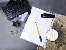 Café avec le stylo, papper blanc, verres, agrafeuse, cactus, café et ordinateur portable, carte de crédit sur la table concrète a images libres de droits