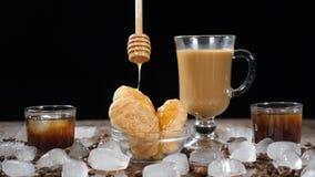 Café avec les croissants délicieux de la glace Miel liquide clair chaud versant vers le bas sur le dessert dans le mouvement lent banque de vidéos