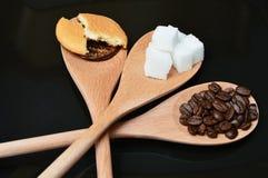 Café, azúcar y torta anaranjada en la cuchara de madera Imagen de archivo