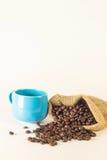 Café azul da caneca com os sacos do saco de feijões de café no fundo branco Fotografia de Stock Royalty Free