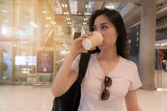 Café bebendo bonito da mulher nova Para a convicção e a azáfama da viagem foto de stock