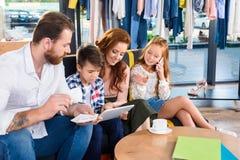 café bebendo da família e utilização da tabuleta digital ao descansar no sofá no boutique imagens de stock