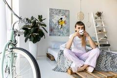 café bebendo da jovem mulher ao descansar na cama na manhã imagens de stock