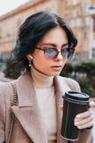 Café bebendo da jovem mulher bonita ao andar ao longo da rua Caf? ir imagens de stock royalty free