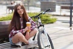 Café bebendo da jovem mulher em uma viagem da bicicleta foto de stock royalty free