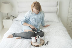 Café bebendo da manhã da menina em uma cama branca que trabalha na tabuleta em meias altas Fotografia de Stock