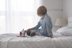 Café bebendo da manhã da menina em uma tabuleta branca da leitura da cama em meias altas Fotografia de Stock