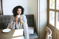 Café bebendo da menina afro-americano nova no restaurante Retrato da senhora de sorriso com o cabelo encaracolado escuro que olha fotografia de stock royalty free