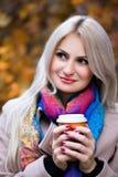 Café bebendo da menina no parque do outono fotografia de stock royalty free
