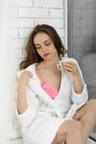 Café bebendo da menina perto de uma janela Fotos de Stock Royalty Free