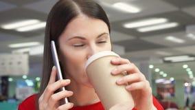 Café bebendo da menina sedento do copo de papel no restaurante do fast food na praça da alimentação Fala no telefone video estoque