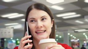 Café bebendo da menina sedento do copo de papel no restaurante do fast food na praça da alimentação Fala no telefone filme