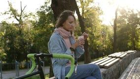 Café bebendo da moça caucasiano em um dia de relaxamento no parque em um banco, tendo a bicicleta ao lado dela A luz do sol da ma video estoque