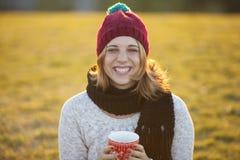 Café bebendo da mulher alegre em um copo do Natal Imagens de Stock