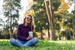 Café bebendo da mulher bonita no parque imagem de stock royalty free