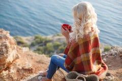 Café bebendo da mulher bonita que senta-se na costa rochosa fotografia de stock royalty free
